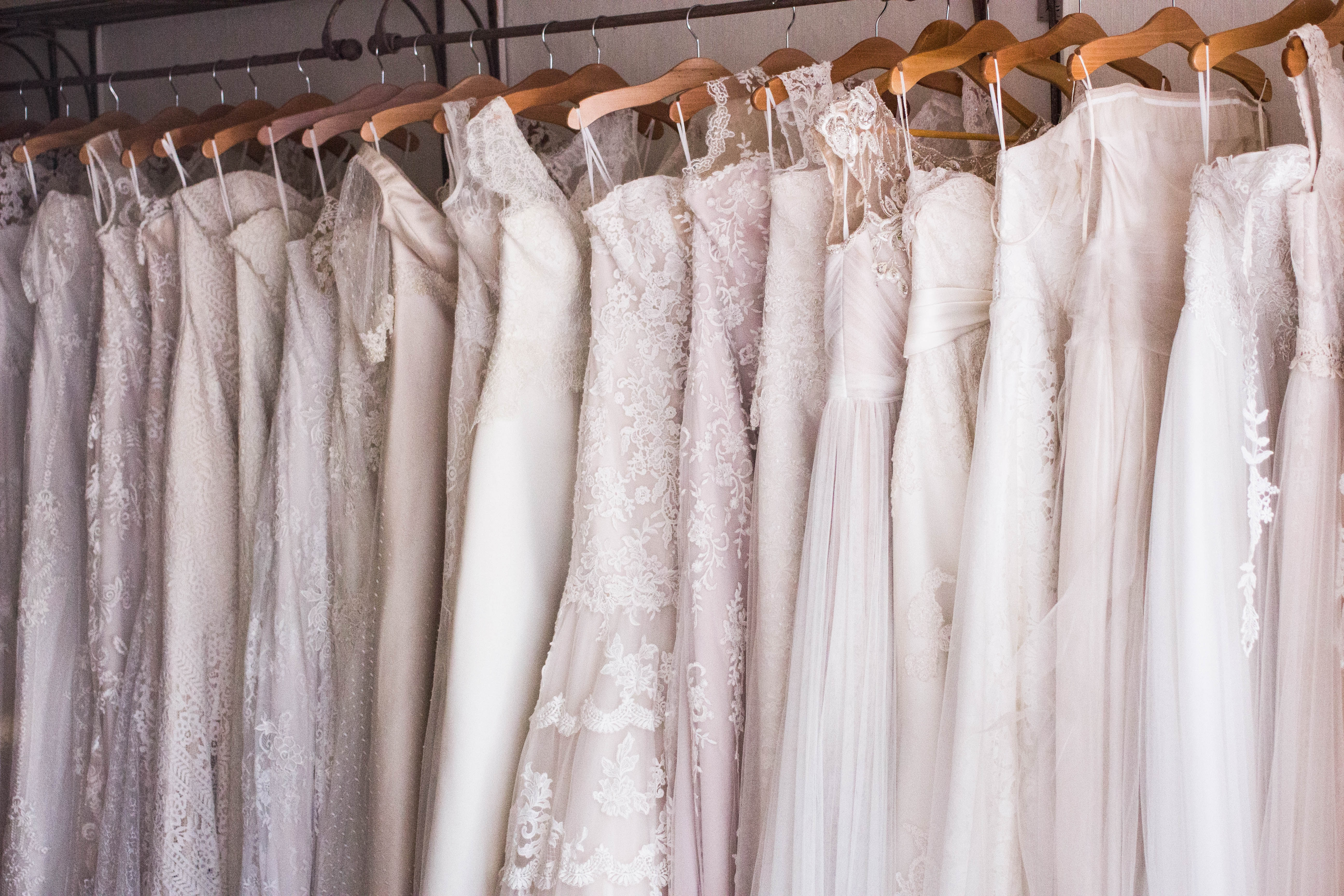 wedding dresses hung up in a row