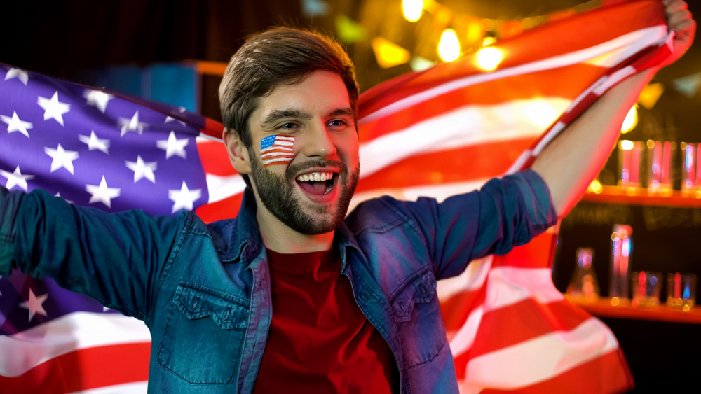 guy holding USA flag behind him and shouting happily