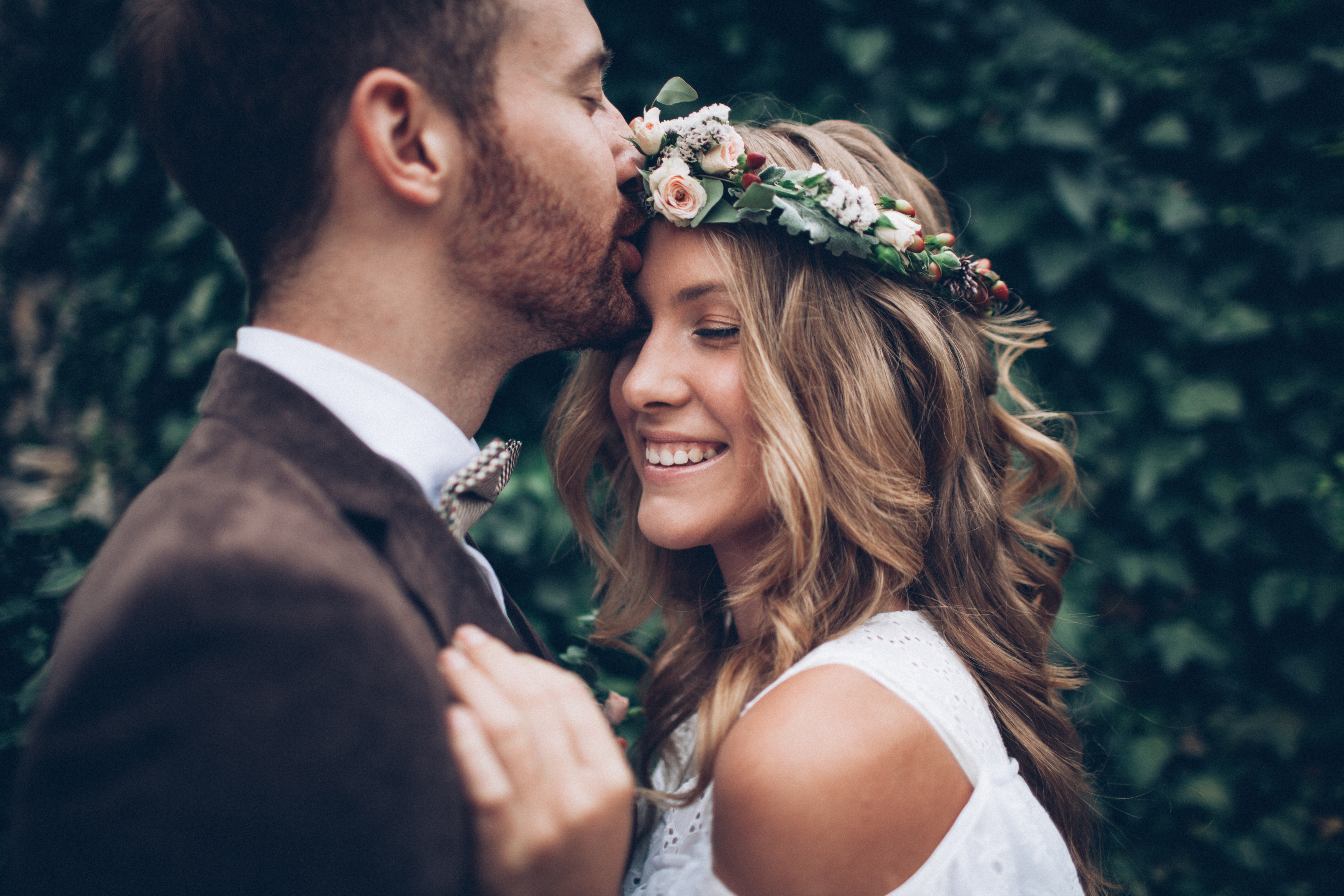 bridal shoot - groom is kissing his smiling bride on the forehead