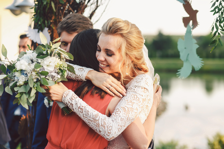 bride hugging a girl friend at her wedding