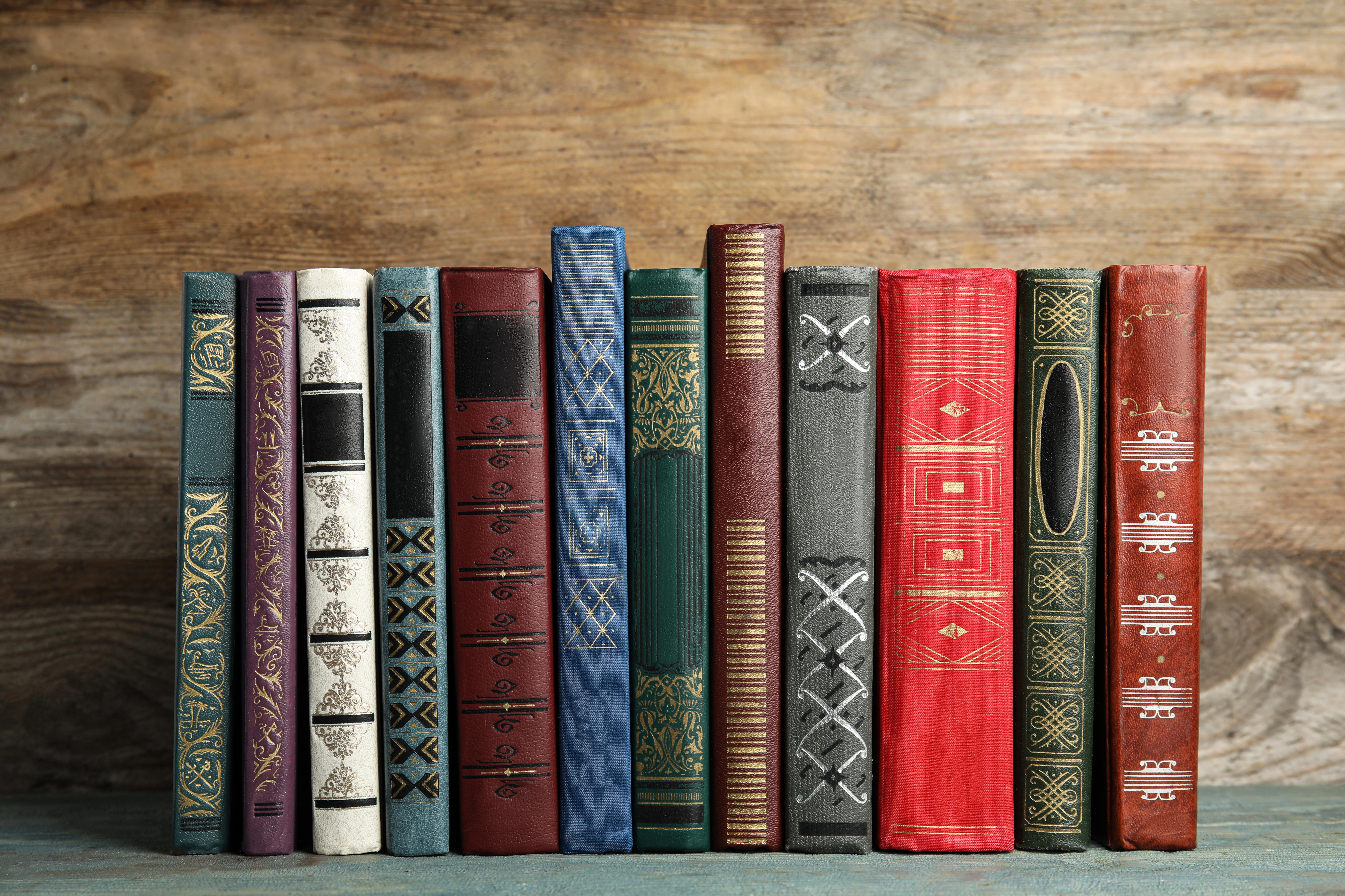 BOOKS LINED UP ON A SHELF.