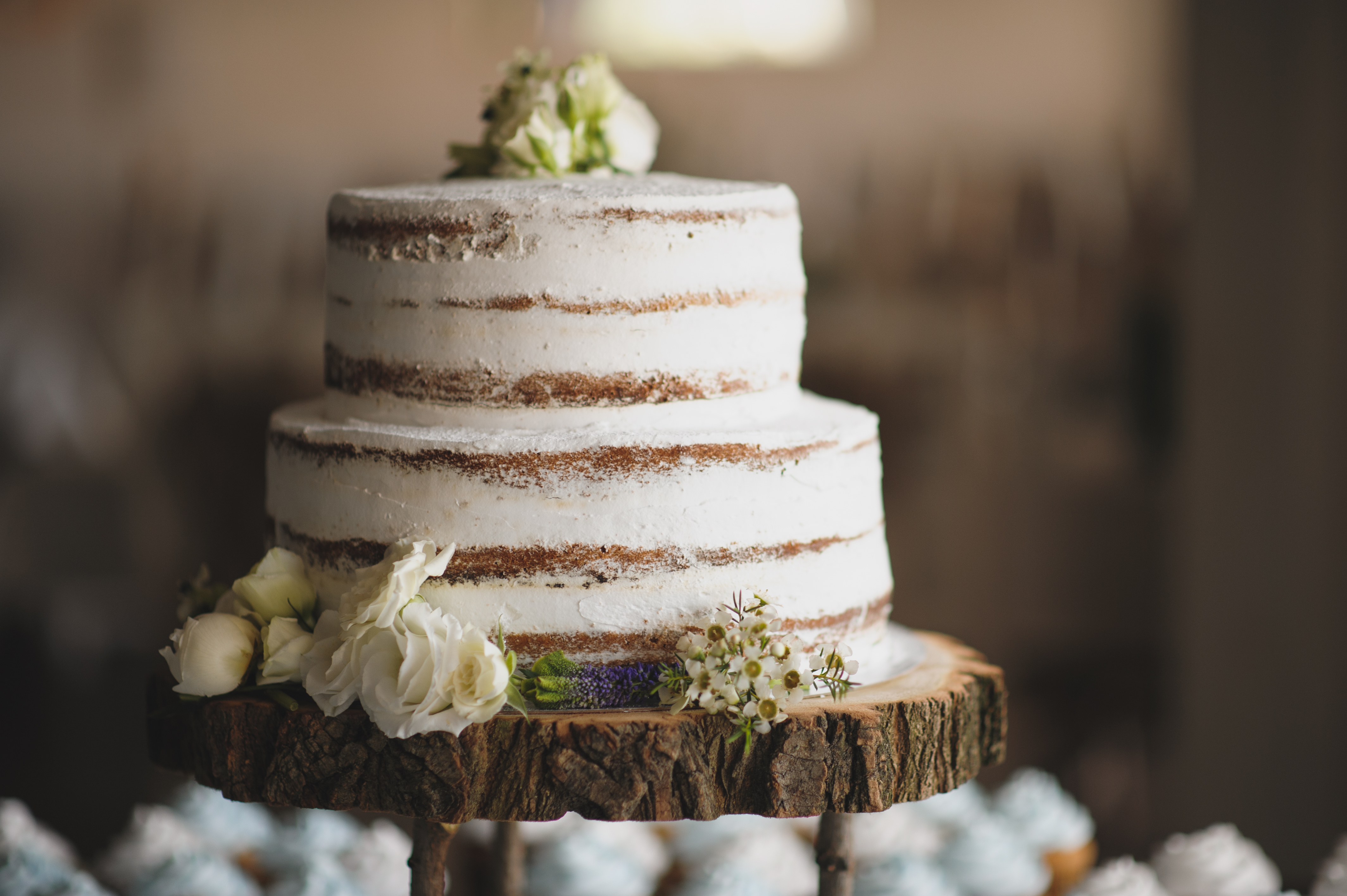 beautiful wedding cake with moss and on top of a piece of a tree trunk