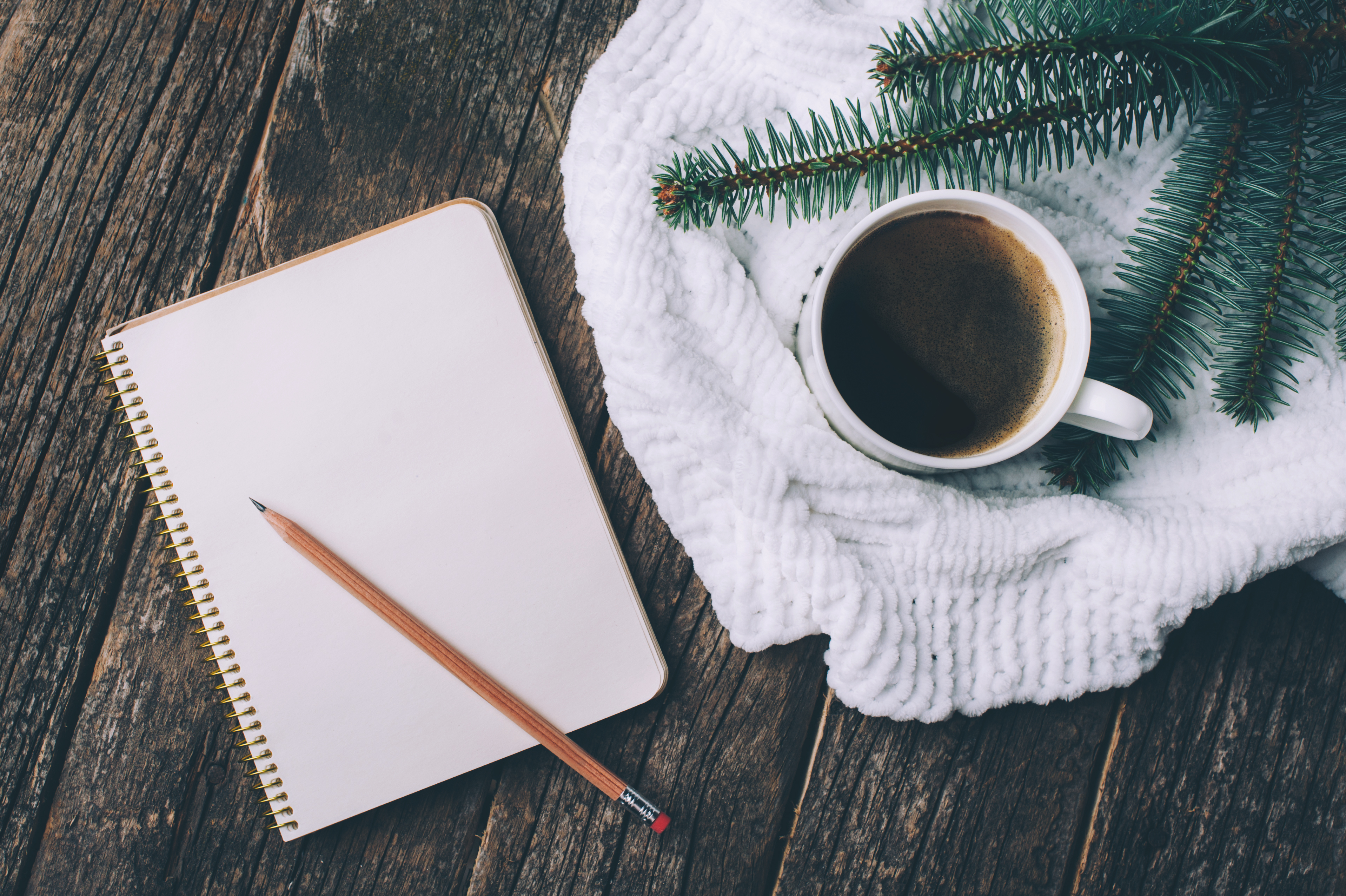 flat lay of notebook with pencil and coffee on a wood table