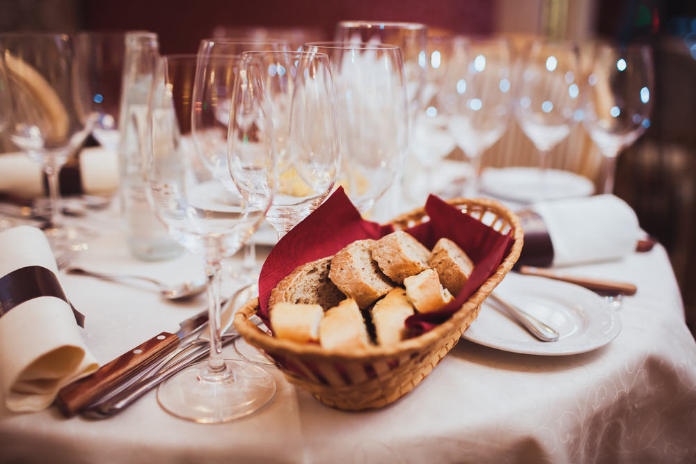 Classy wine and champagne glasses with a bread basket on a white linens.