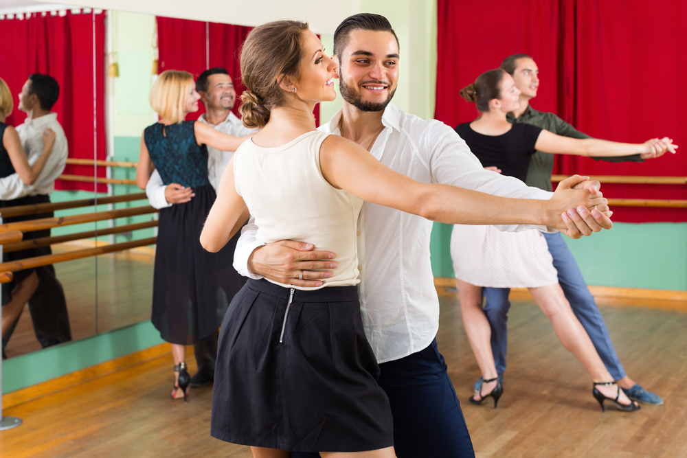 Three couples learn how to waltz in a studio.