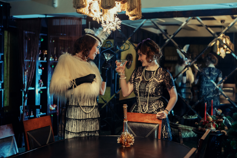 Two women dressed in 1920's American attire cheer in a dark lit bar.