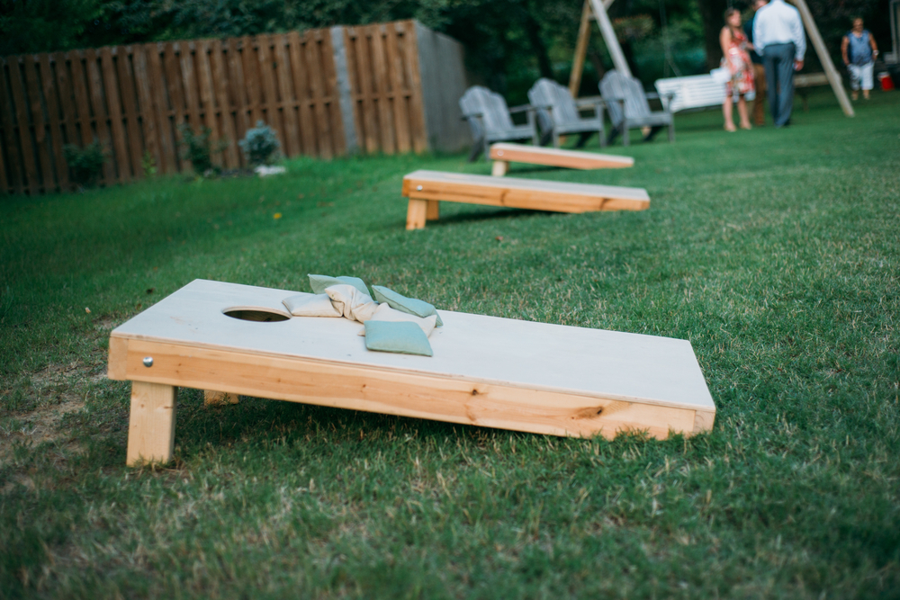 A row of corn hole boards in a backyard.
