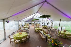 Green indoor tent event with tables