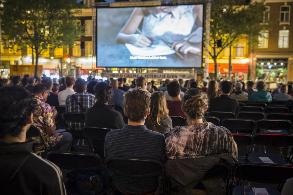 Families watch a movie on a large screen in a park.