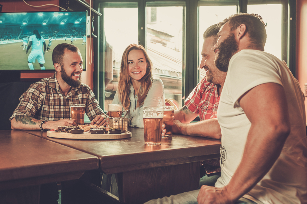 Men and women enjoy beer and company at a bar while watching soccer.