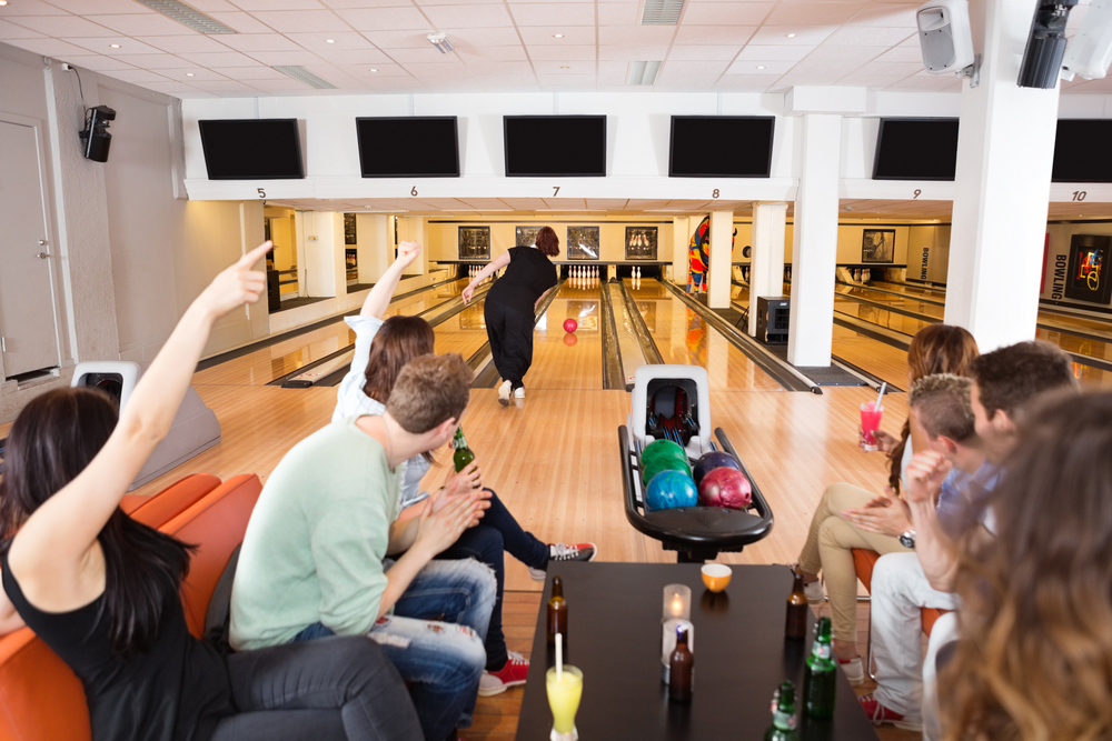 A group of young friends cheer their friend as she bowls.