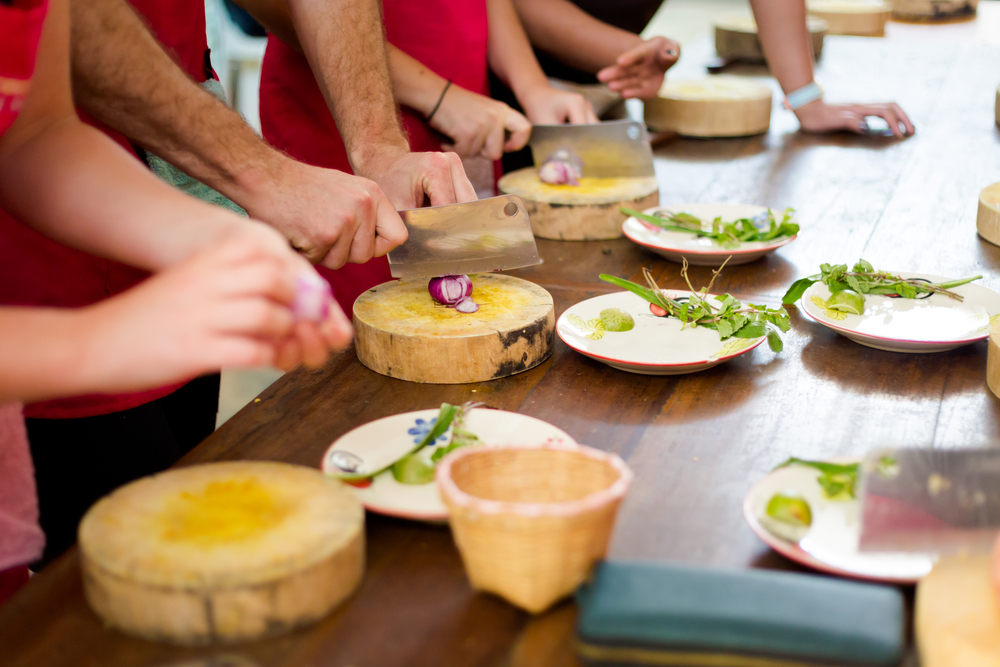 A group of adults take a cooking class together.
