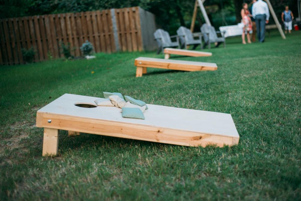 A row of corn hole boards in a backyard.