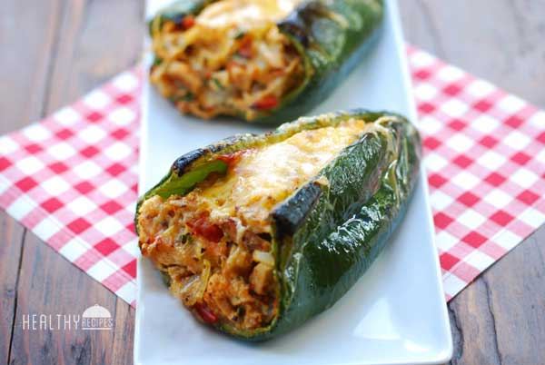 Two stuffed poblano peppers it on a tray on a picnic bench.