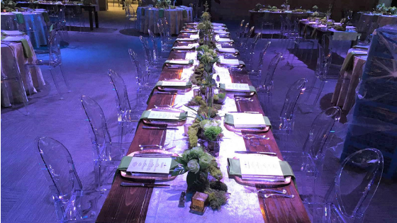 a wedding reception dinner table with centerpiece and transparent chairs