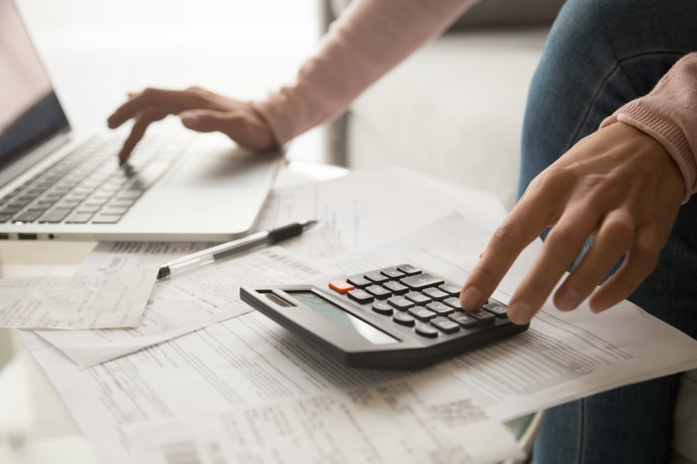 women with a calculator and laptop budgeting